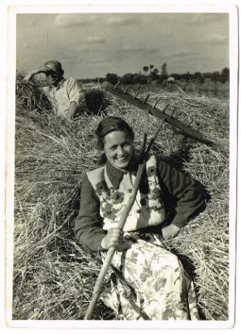 czarno-białe zdjęcie przedstawiające dziewczynę z widłami na sianie